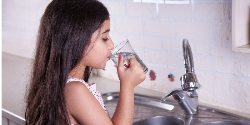 Tap water being drunk by a pretty little girl