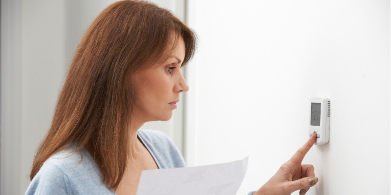 Woman lower thermostat with hydro bill in hand